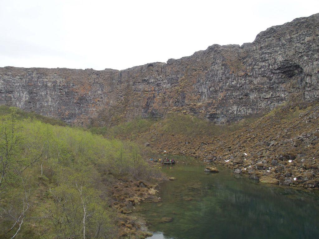 huffoermige Felswand in Island mit grünem See