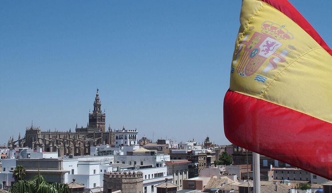 Die spanische Flagge weht vor dem Panorama von Sevilla